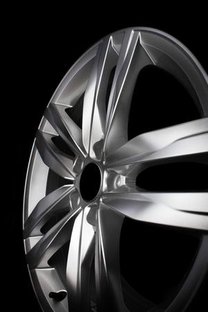 Modern aluminium alloy car rim isolated on black background.