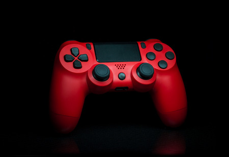 Modern console red gamepad on black background with bottom reflection. Studio lighting shot. Stock Photo