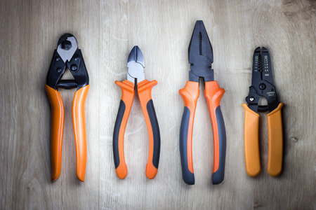 Cutting pliers, gripping pliers, combination pliers, cable cutter. rope cutter and wire stripper. Professional electrician tools on wooden background. Top view.