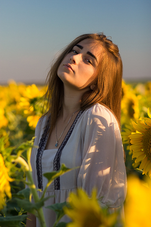 Young girl enjoying nature on the field of sunflowers at sunset, portrait of the beautiful brunette woman with a sunflowers in a sunny summer evening.