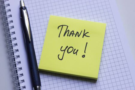 Yellow sticky note on white notepad with the words Thank You Stock Photo