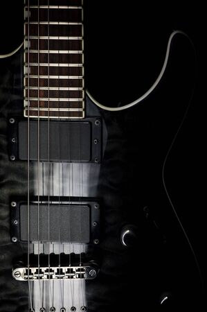 Body of a modern electric black guitar. Close-up photo with light painting technique.