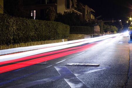 Tracers from passing cars. Night road with ghosts of cars lights. Long exposure. Background. Foto de archivo
