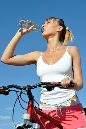 Attractive woman with bike,drinking cold water photo