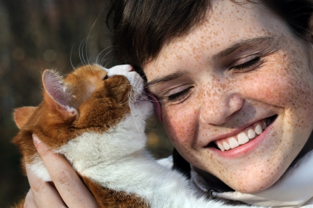freckled: happy freckled girl and funny red cat outdoors Stock Photo