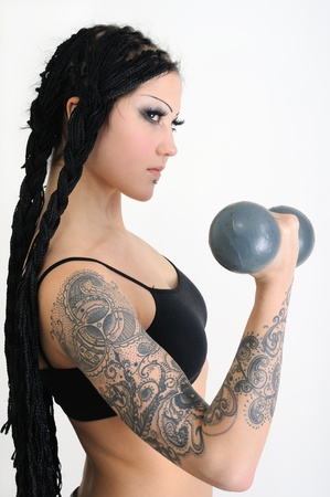 young tattooed stylish woman with dreadlocks,exercising with old dumbbells Banco de Imagens