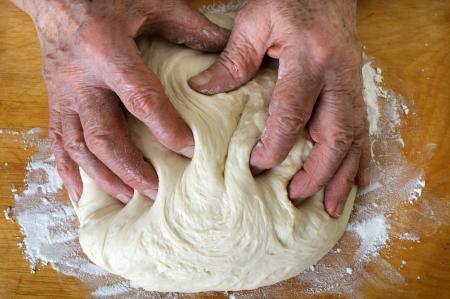 kneading: senior woman make dough in the kitchen Stock Photo