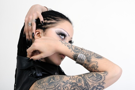 tattoo arm: portrait of young tattooed stylish woman on white background