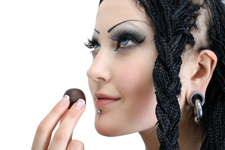young stylish woman with dreadlocks, holding chocolate candy isolated on white