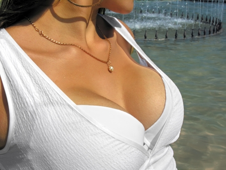beaux seins: belle femme en robe blanche près de la fontaine chaude journée