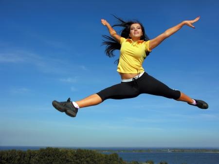 donna volante: atletico giovane donna che vola nel cielo Archivio Fotografico