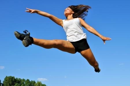salto largo: mujer joven atlético en un salto de longitud sobre fondo de cielo azul