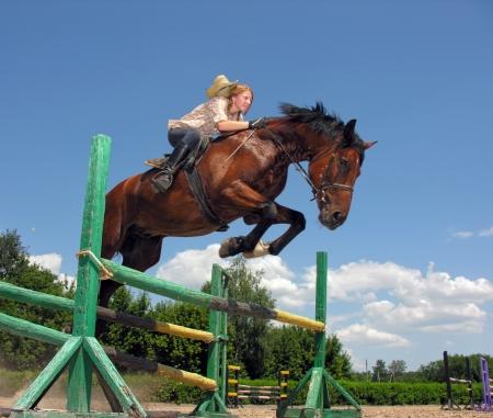 jumping fence: cowgirl joven que salta con el caballo castaño en día de verano