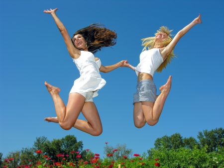 two cheerful girlfriends jumping outdoors in sunny day Stock Photo