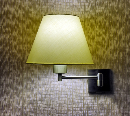 sconce: Sconce on the wall in the darkened room