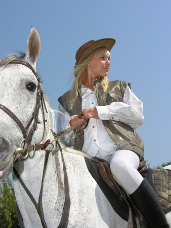 femme et cheval: jeune cow-girl riding en journée ensoleillée