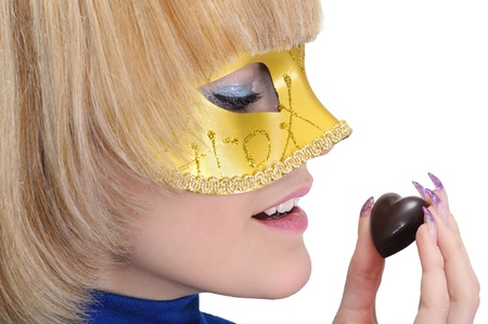 chocolate mask: young woman in carnival mask hold chocolate candy ,isolated on white Stock Photo