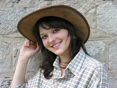 portrait of young cowgirl near the wall