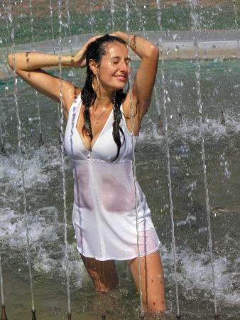 wet woman:           young  woman cooling in the fountain in hot weather Stock Photo