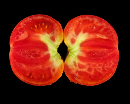 bisected: bisected tomato isolated on black background