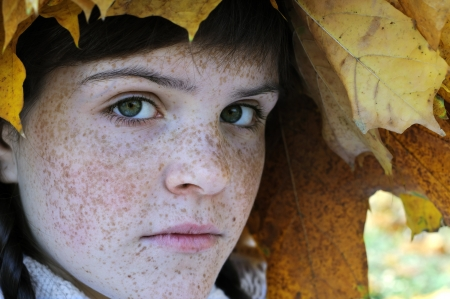 close-up portrait of freckled teenage girl in the autumn park