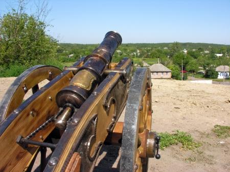 gunnery:           ancient ukrainian cannon against ukrainian landscape on background