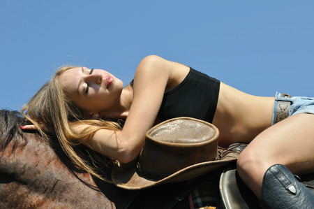 horseback: young attractive  woman relaxing horseback in sunny day Stock Photo