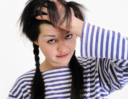 worried young woman touching her hair, looking at camera  photo