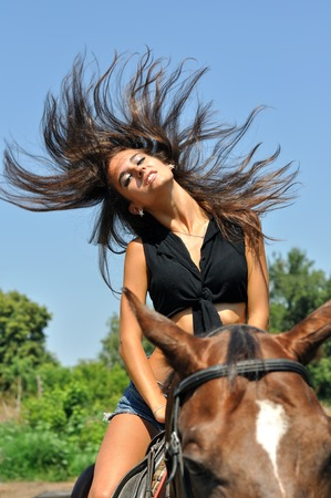 young attractive  woman  horseback riding  in summer day photo
