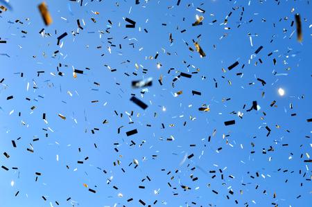 cielo azul: confeti que cae en el festival de la ciudad en el fondo de cielo azul