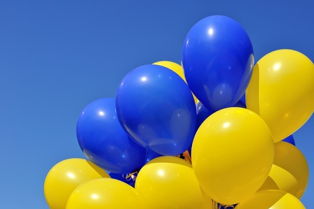 blue and yellow balloons in the city festival on blue sky background Фото со стока