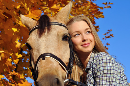 blonde teenage girl: portrait of teenage girl and horse in autumn day