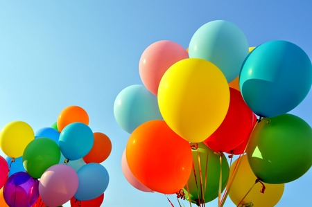fun background: multicolored balloons in the city festival on blue sky background