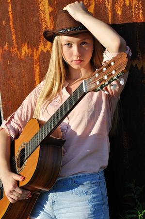 teenage girl: teenage girl holding guitar against old rusty wall background