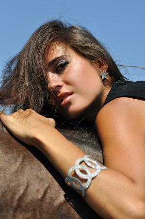 femme brune sexy: jeune femme s�duisante � cheval dans la journ�e ensoleill�e d'�t� Banque d'images