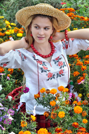 cute teen girl: ukrainian teenage girl in traditional clothes among the flowers Stock Photo