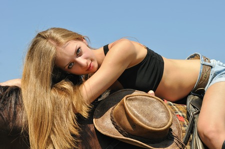 riding: young attractive  woman relaxing horseback in sunny day Stock Photo