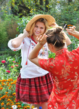 niñas chinas: two teenage girls in traditional ukrainian and chinese  clothes in  the summer landscape