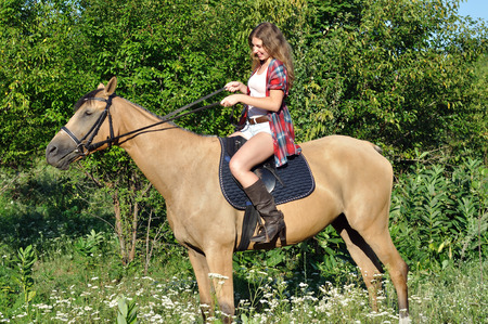 attractive girl horseback riding in the summer sunny day