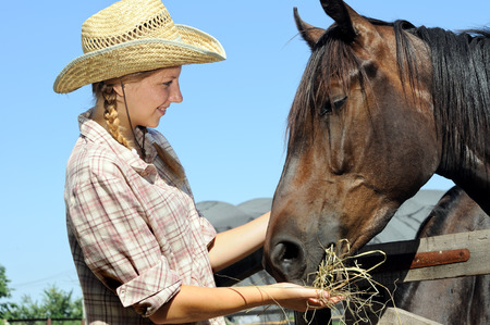 young cowgirl feeding horse in the farm