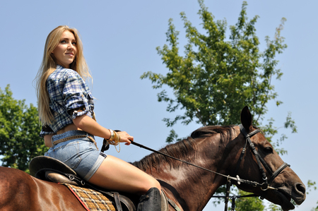 young attractive woman horseback riding in the summer sunny day Stock Photo