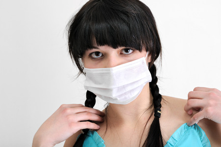 close-up portrait of young woman in protective medical mask on white background, looking at camera