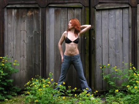 redhead woman in black bra stands near old warehouse in the spring