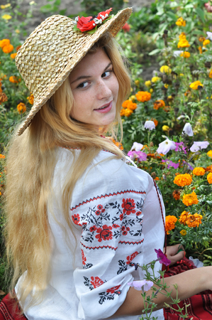 ukrainian teenage girl in traditional clothes among the flowers Stock Photo