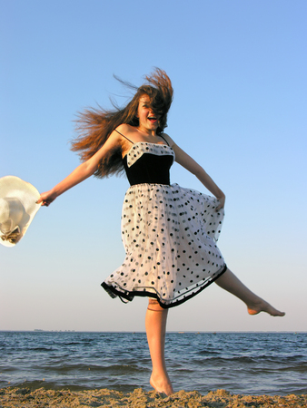 Cheerful young woman at the beach, windy weather, motion blur
