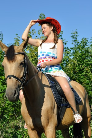 Young attractive woman horseback riding in sunny day, vertical composition