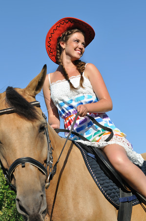 Young attractive woman horseback riding in sunny day