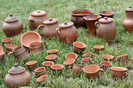 Lots of traditional ukrainian handmade clay pottery production on the green grass Banco de Imagens