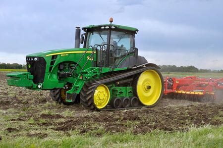 Cherkasy, Ukraine - May 18, 2018: Modern John Deere tractor model 8345RT ploughing an agricultural field at the agricultural exhibition AGROSHOW Editöryel
