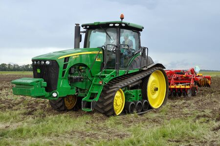 Cherkasy, Ukraine - May 18, 2018: Modern John Deere tractor model 8345RT ploughing an agricultural field with modern plough at the agricultural exhibition AGROSHOW Editöryel